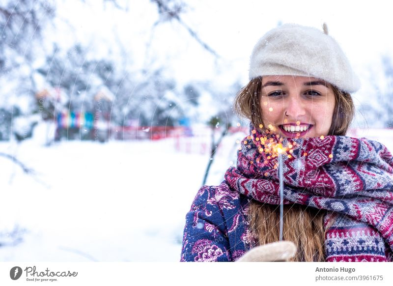 Portrait of a blonde woman wearing a beret, jacket and scarf lighting a sparkler in the snow. snowy snowstorm flare christmas celebration fun happy white year