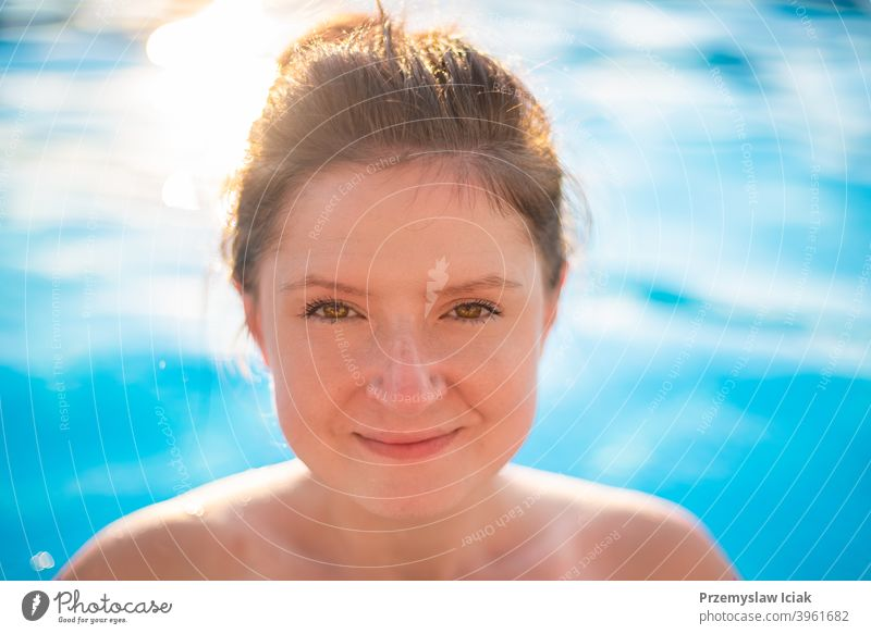 Young woman portrait in swimming pool. fashion candid spa water looking person girl authentic eyes summer face sun bikini caucasian beautiful lifestyle healthy