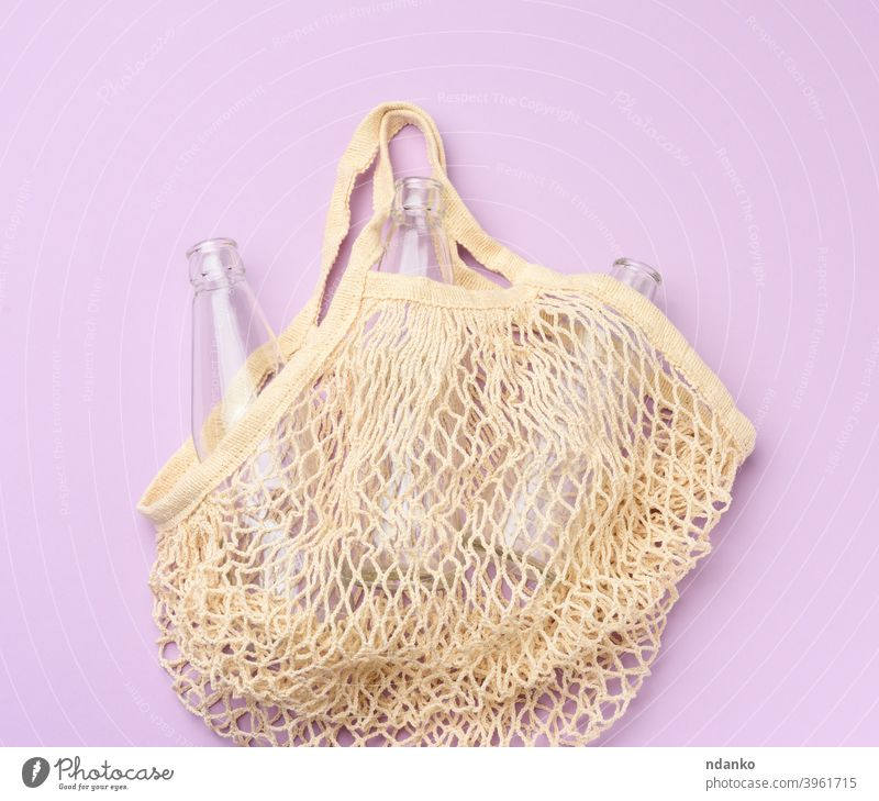 reusable textile shopping bag with empty bottles on a purple background glass grocery handbag lifestyle market mesh bag natural nobody object organic recycle