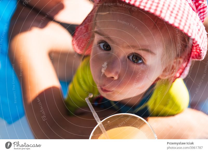 Cute baby girl outside drinking juice with a straw outdoors background beverage thirst family child closeup person reach summer kid nature face sun orange color