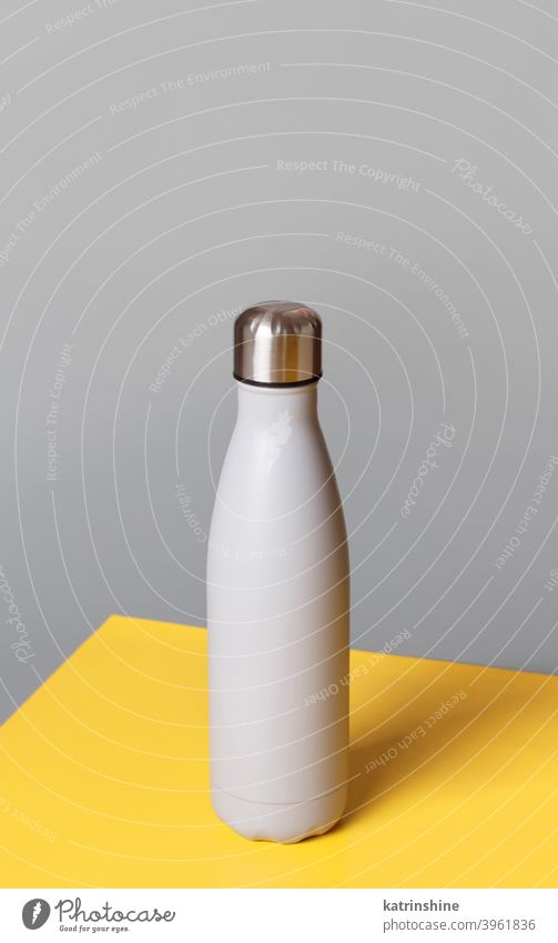 Grey reusable steel bottle on grey and yellow background monochrome mockup insulated ecologic water thermo aluminum blank close up concept copy space