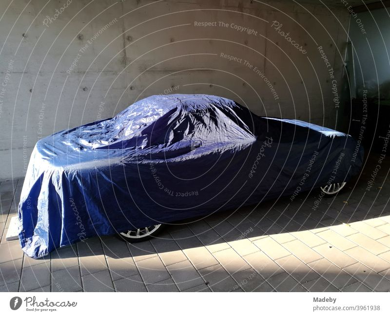 Sportwagen Cabriolet abgedeckt mit einer blauen Plane aus Kunststoff bei Sonnenschein in einem modernen Carport aus Beton Auto Roadster Schutzhülle Abdeckplane