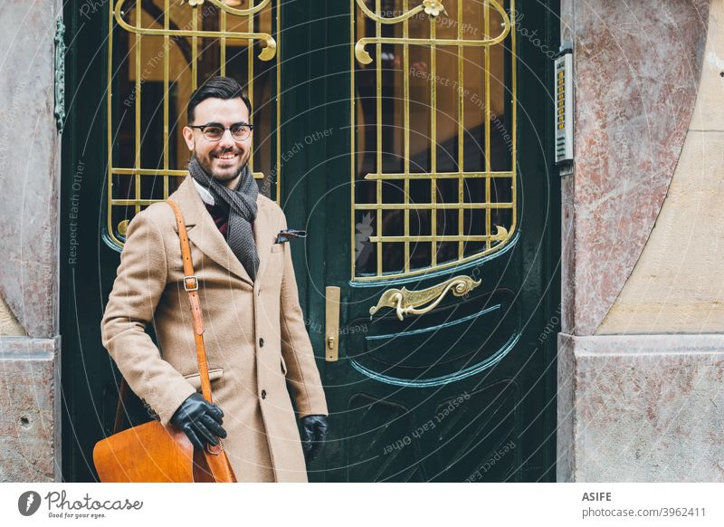 Young elegant bussiness man in a retro style fashion at the front door young dandy street portrait attractive modern winter gentleman bearded smart business