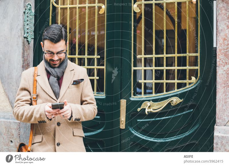 Young elegant man in a retro style using his smartphone at the front door young dandy smart phone cell phone mobile fashion street portrait technology app