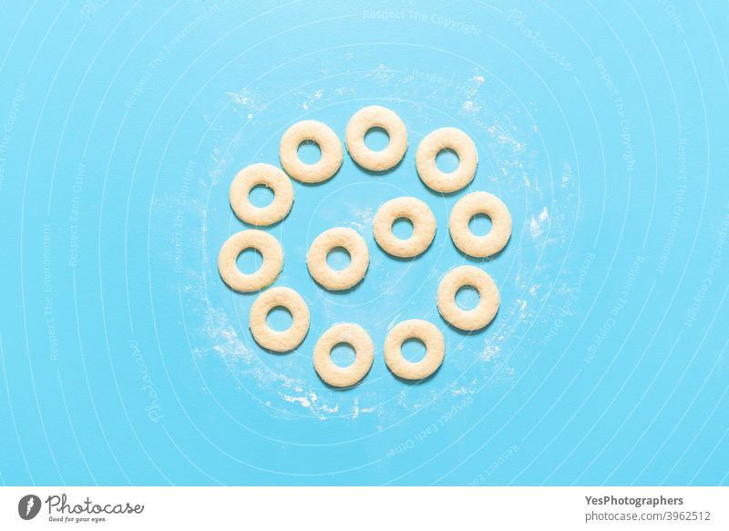 Cooking donuts process. Making American doughnuts. Homemade sweet dough top view aligned american baking blue background breakfast cake circle shape