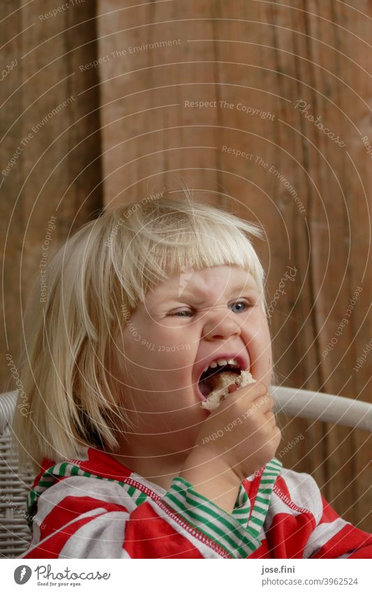 Mh delicious bread Girl cute Joy Grimace Impish fringe hairstyle portrait Blonde little girl Child Infancy Cute Brash Eating To enjoy excited spellbound