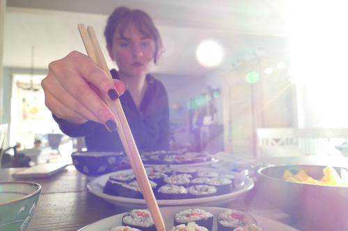 Young woman eating vegetarian homemade sushi, with chopsticks, light coming from right. Japanese Roll Rice Asian traditionally Wasabi Ginger Wooden table