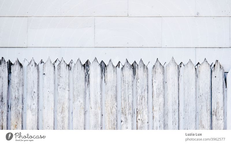 Facade and forms, an old wooden fence with sharp jags in front of facade panels, which have also been affected by the ravages of time. Fence Fence posts