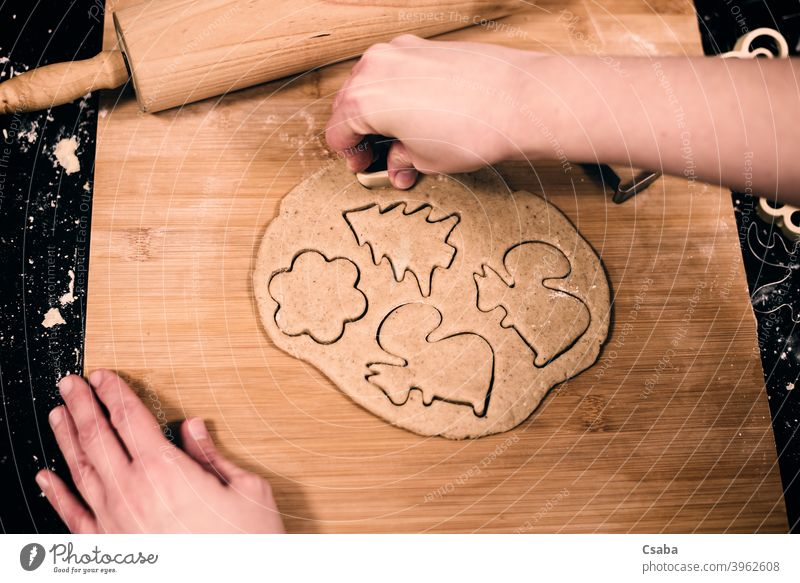 Top view of woman's hands making gingerbread preparing top homemade cookie sweet food raw dough rolling pin dessert pastry christmas cutter traditional