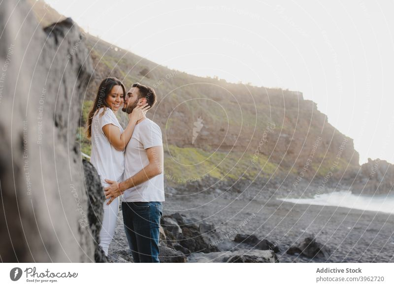 Loving couple embracing on rocky seashore romantic love embrace kiss coast beach together fondness happy young tenerife island canary spain relationship