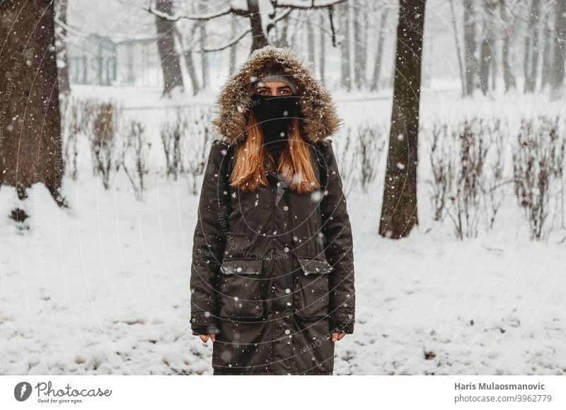 woman with face mask standing outdoors in snow adult alone attractive beautiful black brunette cold confident coronavirus covid-19 cute fashion female forest