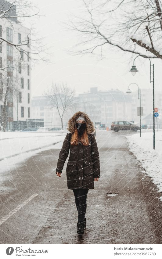 woman with face mask walking outdoors in snow adult alone attractive beautiful black brunette cold confident coronavirus covid-19 cute empty empty city fashion