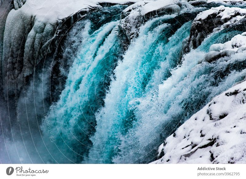 Amazing waterfall in mountainous terrain in winter flow stream rapid snow rocky landscape iceland nature scenery picturesque environment cold energy magnificent
