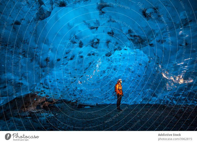 Traveler standing in ice cave in winter traveler adventure explorer light cold frozen nature iceland tourism blue landscape rock arctic scenic vacation polar