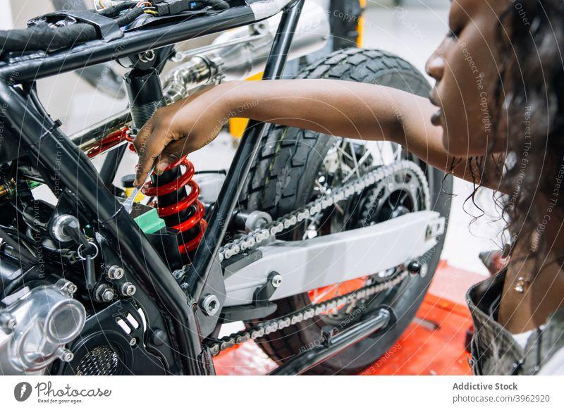 Black woman repairing motorcycle in garage mechanic fix motorbike workshop wrench spanner service female ethnic black african american technician custom