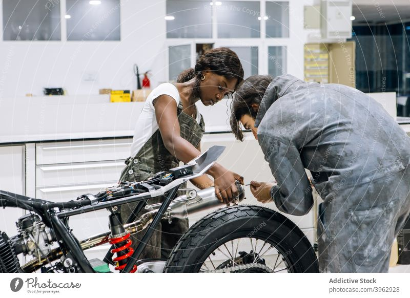 Mechanics fixing exhaust system of motorcycle together mechanic workshop muffler repair multiethnic multiracial african american diverse black tool cabinet