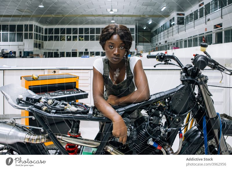 Black woman with motorcycle working in workshop mechanic motorbike custom professional vehicle repair assemble female african american black ethnic job