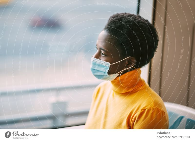 Dubai, UAE, November 2020 A young African woman wearing a protective mask rides on a bus and looks out the window. Coronavirus, social distance. Side view