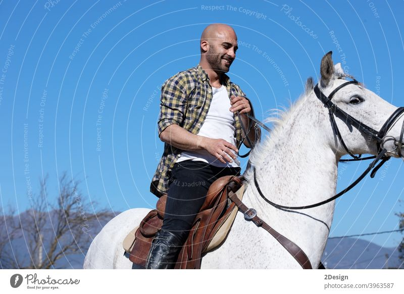 Young guy in casual outfit riding white horse on sandy ground equestrian equine horizontal obedient ranch creature dressage horseback jockey male mammal mare