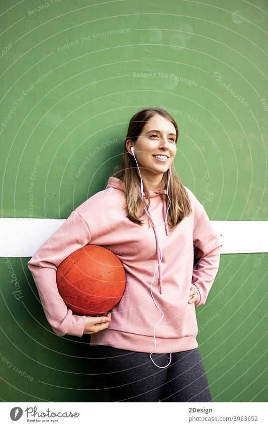 young long haired woman holding a basket ball against green wall sport person basketball fitness training athlete female girl player exercise healthy lifestyle