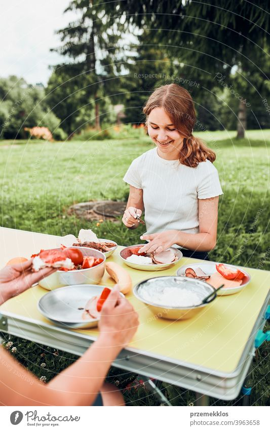 Family having breakfast outdoors on camping during summer vacation authentic real banana cooked meat slow living outdoor table setting outdoor activities