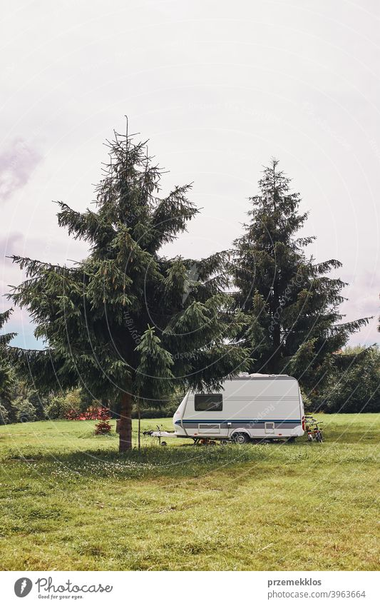 Caravan left among the pine trees on campsite exploring recreation house trip car transport grass ground field camping recreational equipment van life