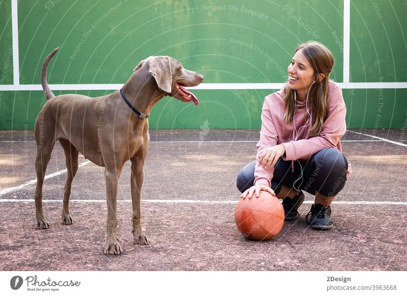 Young woman holding ball posing with her dog sport person basketball female girl player pet exercise young healthy lifestyle fit game body happy pretty