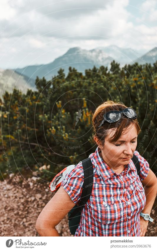 Woman with backpack hiking in a mountains, actively spending summer vacation, having break after going up on a hill activity adventure female freedom green