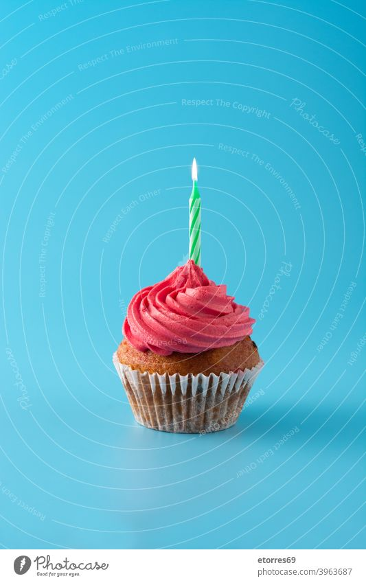 Pink birthday cupcake on blue background bakery buttercream candle celebrate concept creamy decorated delicious dessert food frosting gourmet holiday muffin