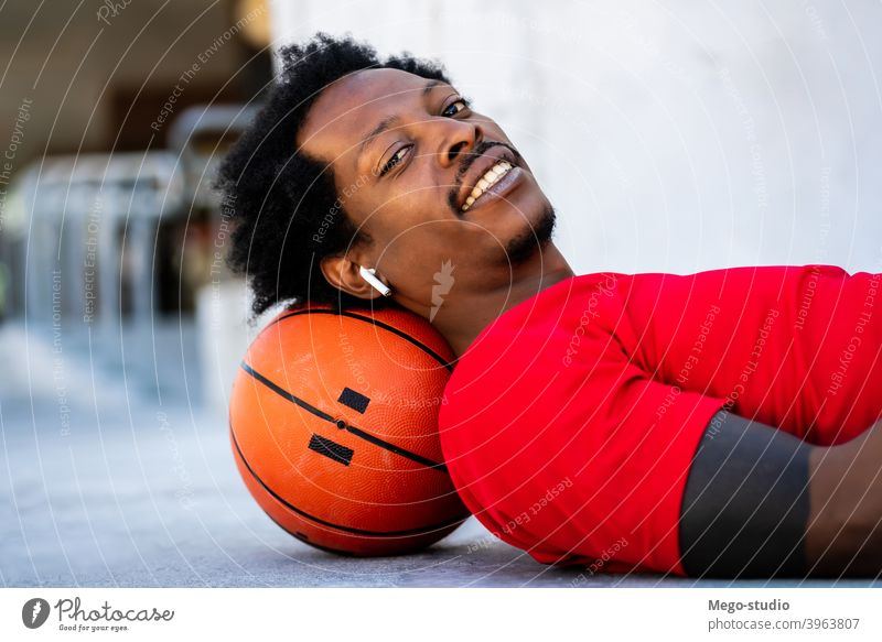 Afro athlete man laying on floor after training. sport basketball urban athletic outdoor standing enjoy expression outdoors active hand exercise recreation