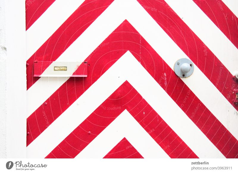 Red and white angles on a door White red and white decoration Decoration Jewellery graphic apartment door Entrance Access Mailbox mailbox flap address delivery