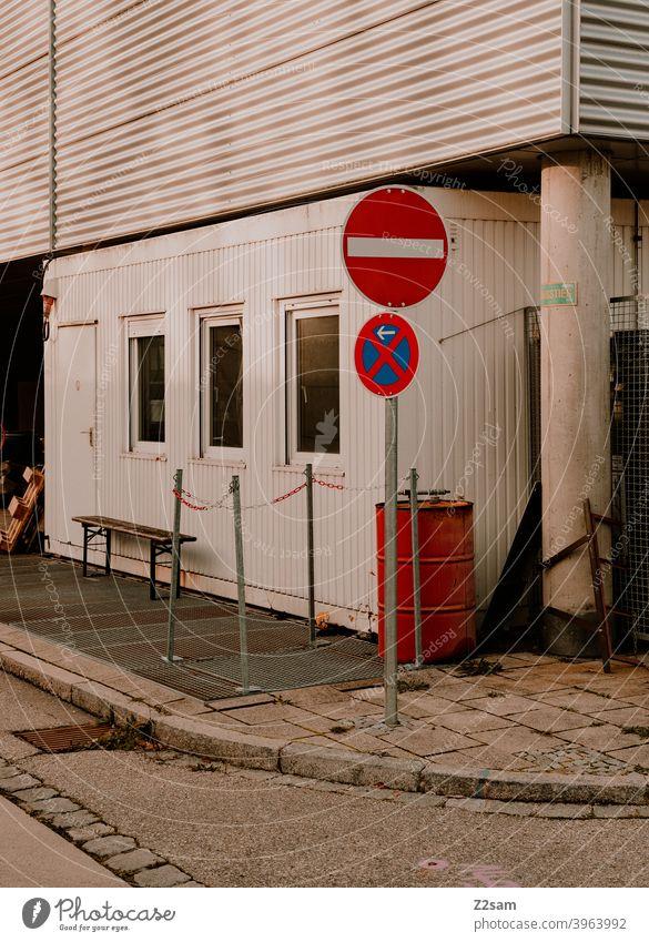 Halteverbotsschid in Industrieumgebung street photography schild fußgänger industrie industriegebiet schilder zeichen mülltonne beton stadt urban warme farben