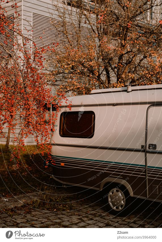 Wohnwagen in Herbstlandschaft street photography Still Life design art background Object photography colorful Structures and shapes geometric graphic parkplatz