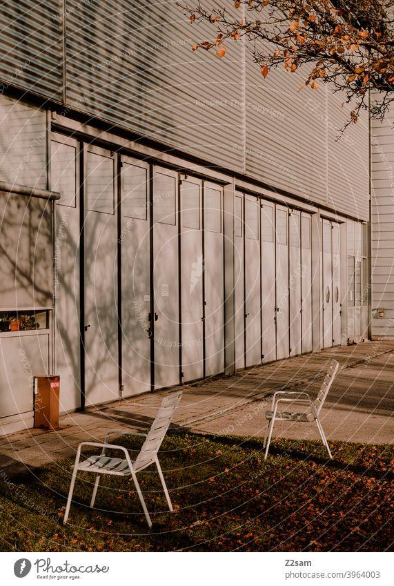Stühle im Aussenbereich einer Industriehalle industriehalle stühle einfahrt tore produktion warme farbe pause erholung mittagspause bäume schatten licht herbst