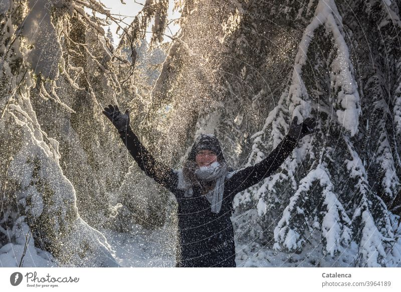 The young woman is happy about the shower of snow that falls from the firs and raises her arms coniferous Forest Weather Snow Winter chill Day daylight Tree