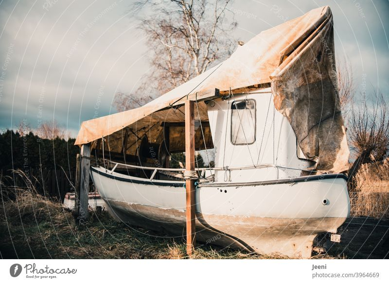 A fishing boat moored ashore for the winter in a small fishing harbour Fishing village Fishing boat covered bring ashore drained ship BUK Port side Starbord