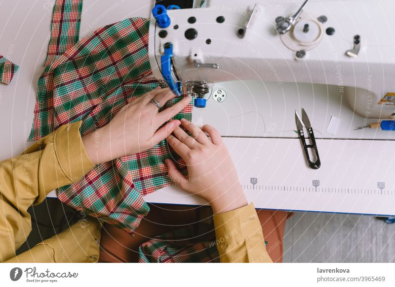 Top view of woman working with sewing machine in her workshop fabric tailor material seamstress clothing needle craft thread textile business worker dress
