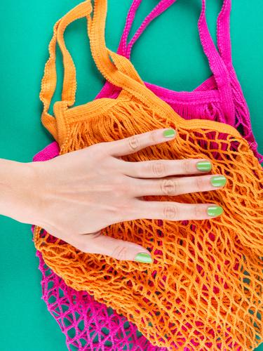 Zero waste. Color mesh shopping bags on green reusable zero waste mesh bag hands food bulk produce sustainability pink trendy cotton manicure plastic free
