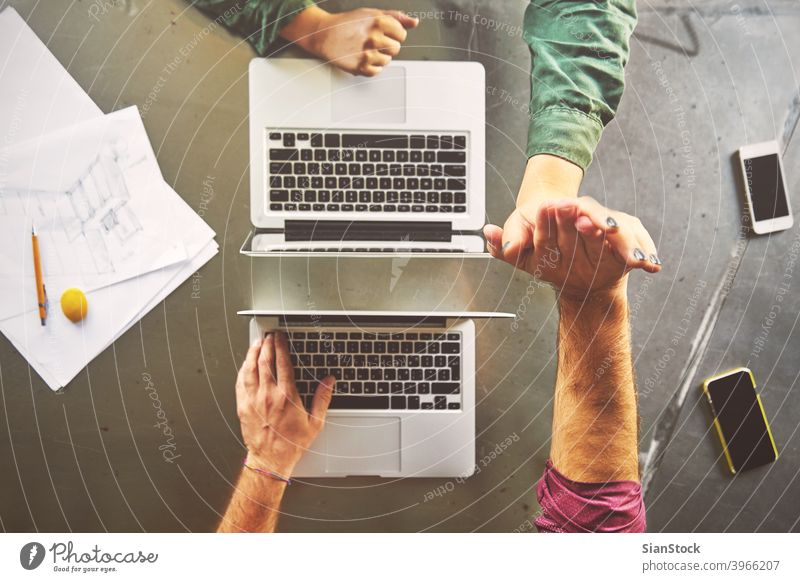 Top view of architects giving high-five while working at computer in office laptop business workplace hands keyboard desk table technology notebook coffee up
