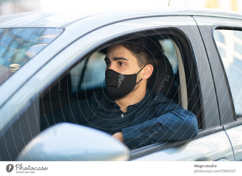 Young man driving his car. face mask drive sitting leisure road seat travel protective mask facemask city traffic medical mask outdoors concept healthcare adult