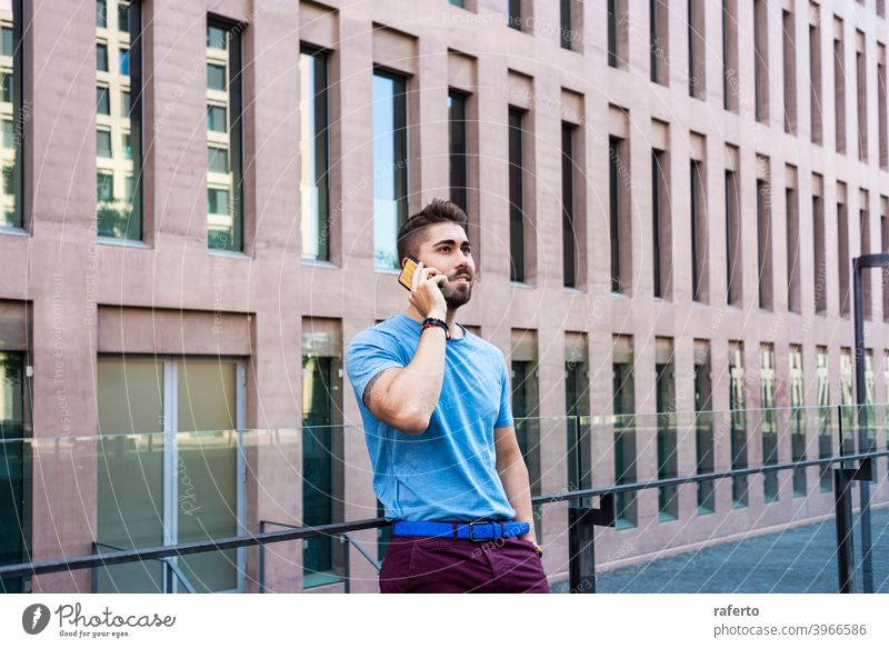 Portrait of cheerful modern businessman speaking by phone and smiling while standing outdoors building talking mobile city male photogenic adult people street