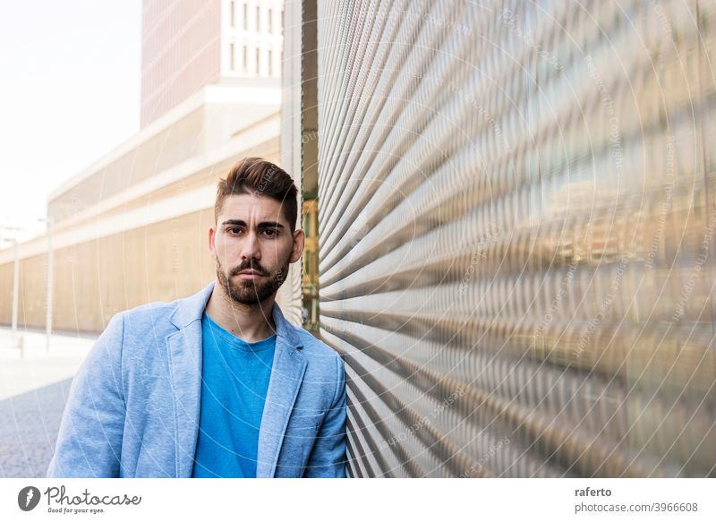 Young bearded man in urban background wearing casual clothes while leaning on a wall and looking at camera cool style portrait guy 1 photogenic stylish modern