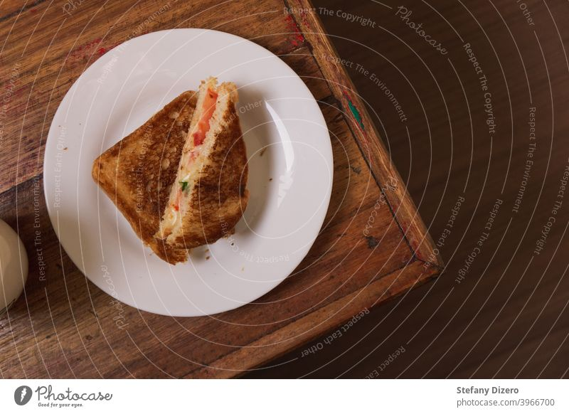 Toasted cheese sandwich on a white plate, arranged on a corner of a wooden table Sandwich Cheese Lunch Snack Wood Table felicious Tasty Tomato Food