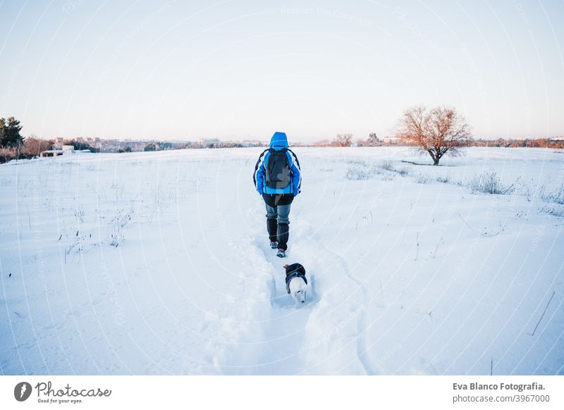 back view of happy man in snowy mountain at sunset. Travel and sport outdoors concept. Winter season dog jack russell travel owner pet love together hiking