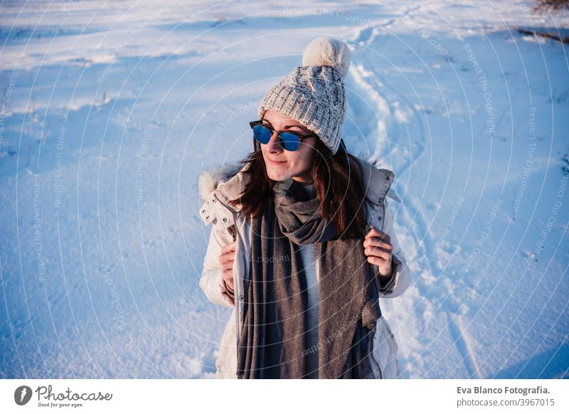 happy young woman hiking in snowy mountain wearing modern coat at sunset. winter season. nature cold caucasian forest wanderlust travel walk hiker mood
