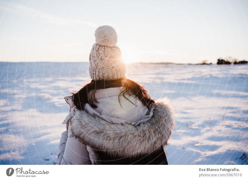 back view of woman in snowy mountain wearing modern coat at sunset. winter season. nature hiking cold caucasian forest wanderlust travel walk hiker tour tourism