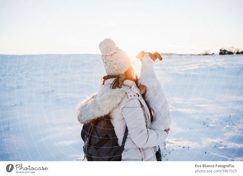 back view of woman in snowy mountain wearing modern coat at sunset. Holding cute jack russell dog in arms. winter season. nature at sunset travel owner pet love