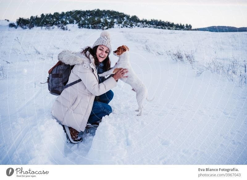 happy woman in snowy mountain wearing modern coat at sunset. Holding cute jack russell dog in arms. winter season. nature at sunset travel owner pet love