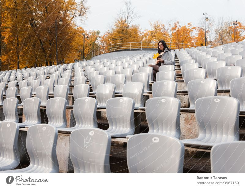 young girl in a gray coat sits on a seat of an empty stadium woman sitting autumn female alone sadness lonely caucasian beautiful emotion outdoor person people
