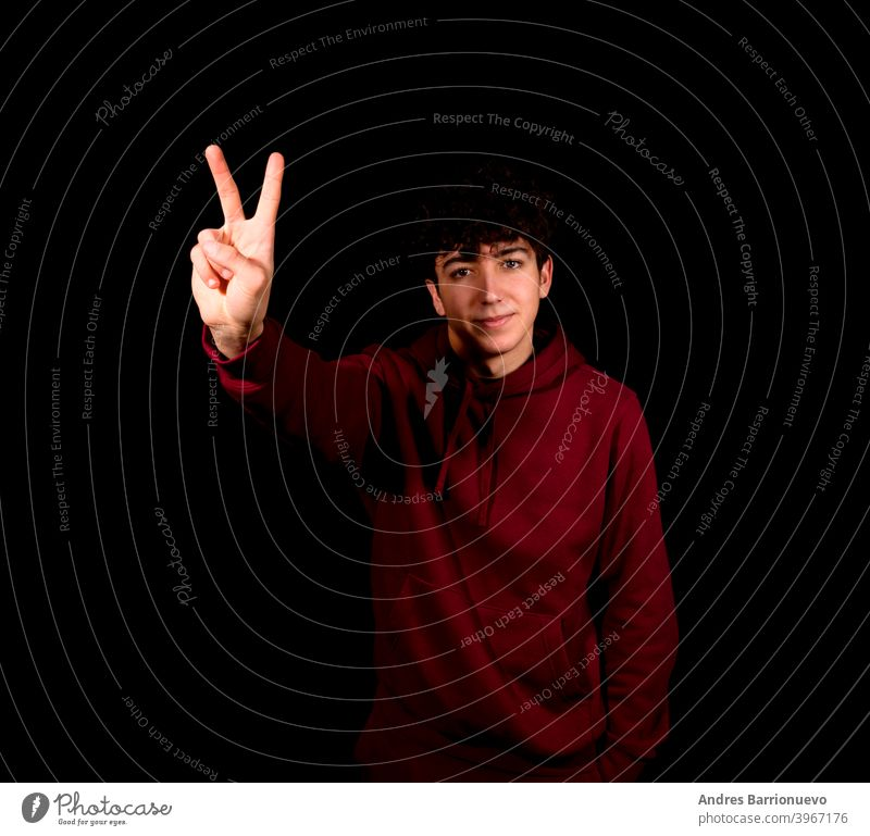 Attractive young man making the victory symbol on a black studio background happy caucasian photogenic gesture shirt beautiful positive adult face peace